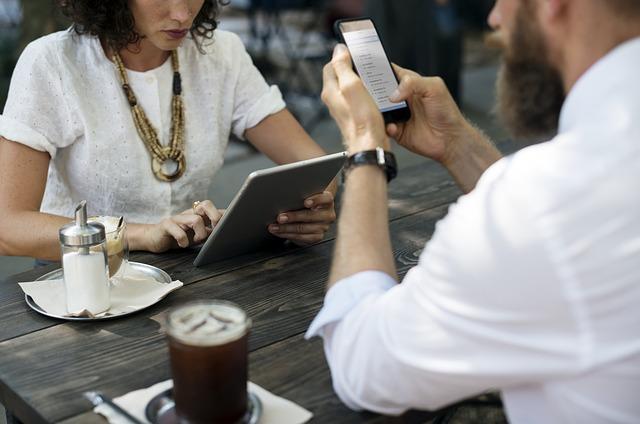 muž a žena sedí spolu u venkovního stolu – ona na internetu na notebooku, on na mobilním